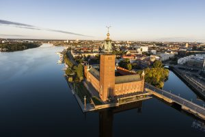 View from above of large building with a tower by the water. Air-photo.